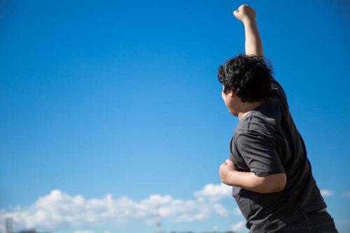 空に向かって手を上げる男性